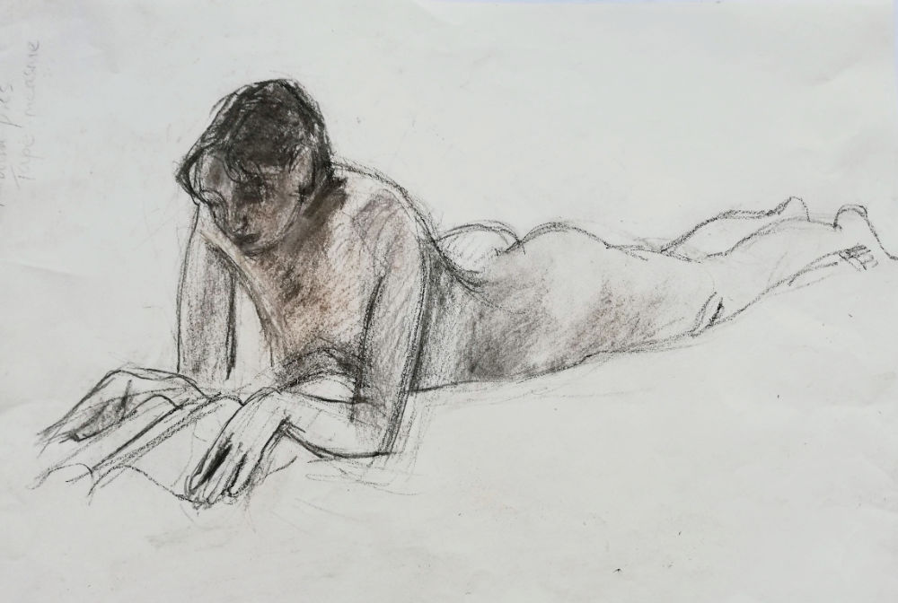 Model lying on her front reading