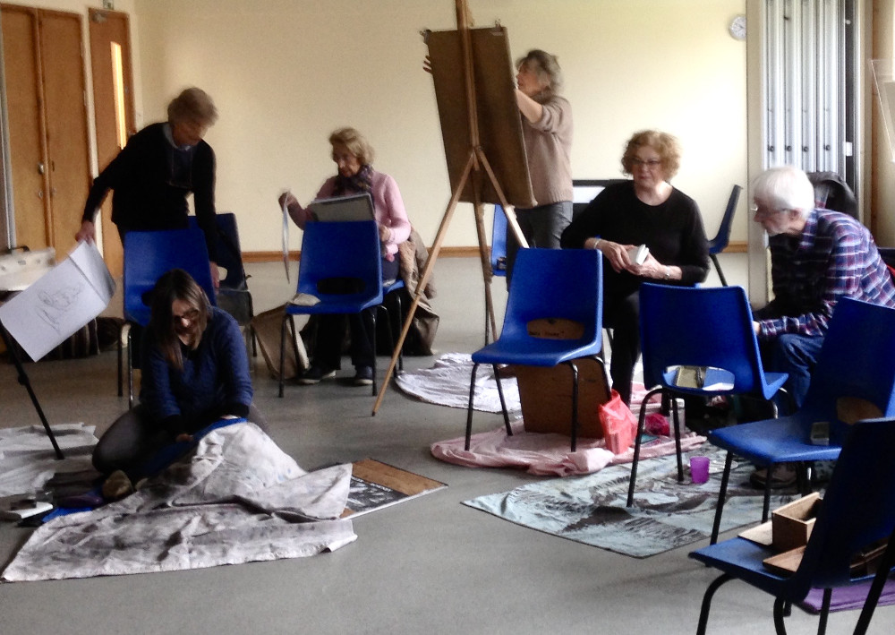 Some members chose to draw on the floor while others stood at an easel